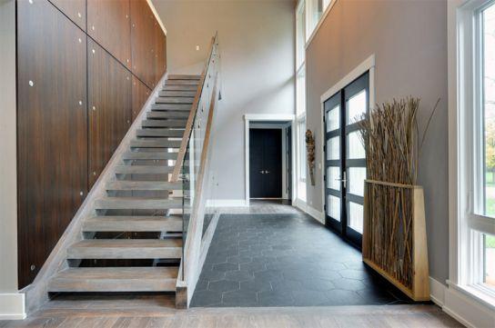 Cầu thang với tông màu trắng như trong thiết kế trong hình ảnh này phù hợp với mọi căn nhà, cửa sổ và cửa đi có nhiều ô kính giúp ánh sáng tràn vào ngôi nhà. Việc trang trí cũng tạo nên thành công cho mẫu thiết kế này.
